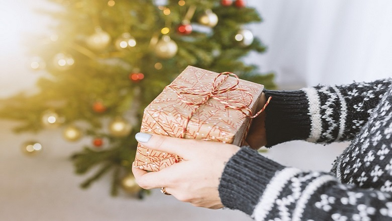 hands offering a present near a Christmas tree