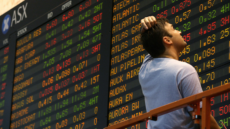 man looking at the ASX ticker board