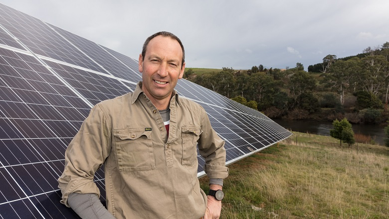 Farmer in front of solar panels