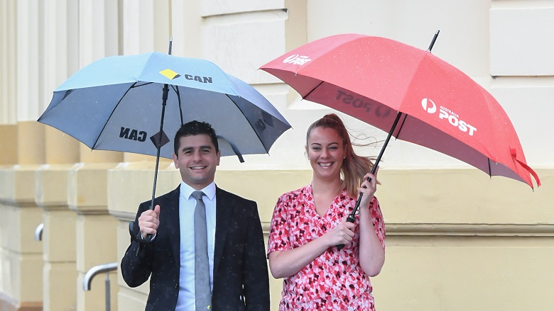 Australia Post and CBA employees with umbrellas