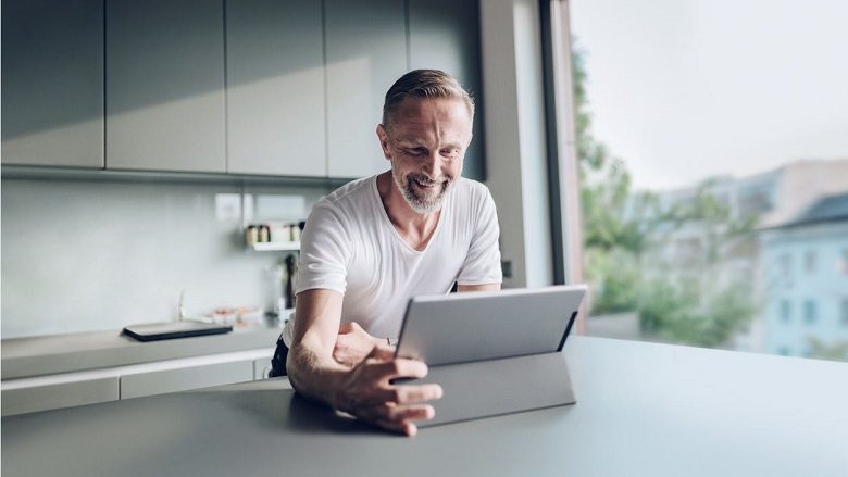 Man in kitchen looking at laptop screen
