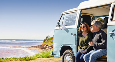 An older couple sitting in a Kombi van parked at a beach