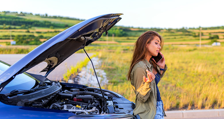 A young woman calling for help on her phone with her broken down car