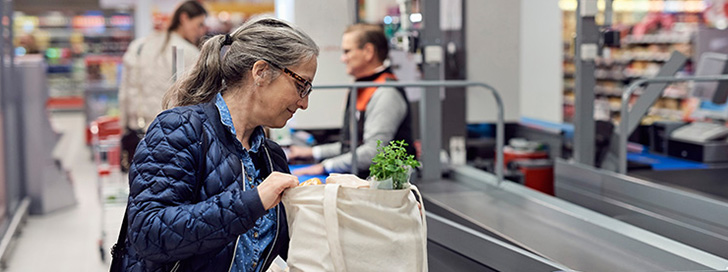 Senior lady paying for good at supermarket