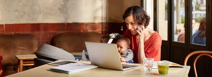 Woman with baby on phone with laptop working