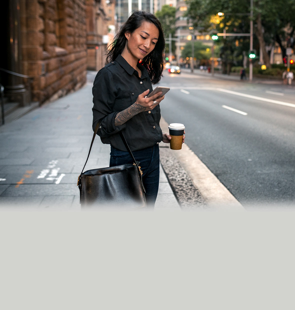 Woman standing on the kerb in a city about to cross the road, getting a phone notification