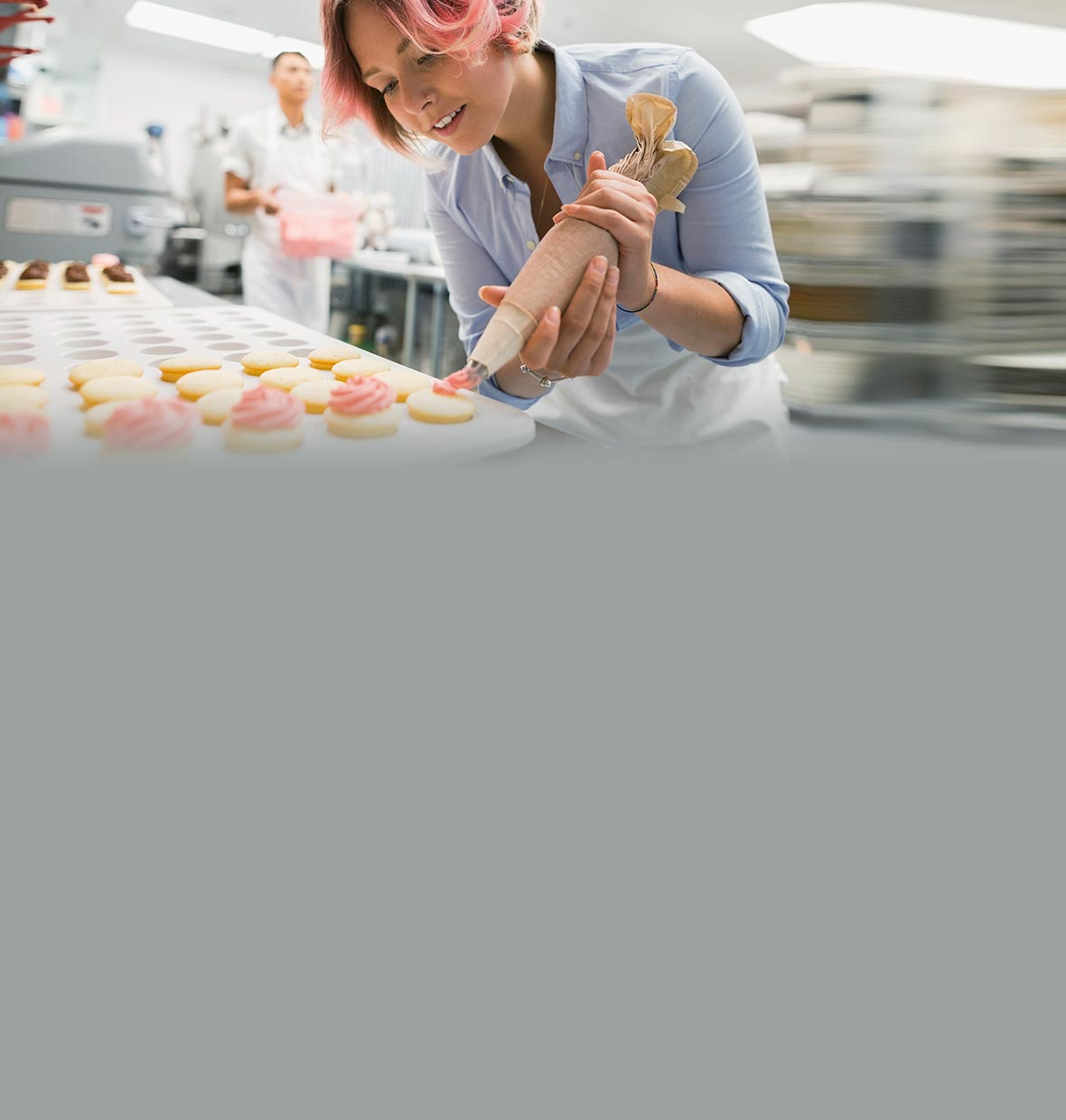 Woman piping icing onto cupcakes in a small business commercial kitchen