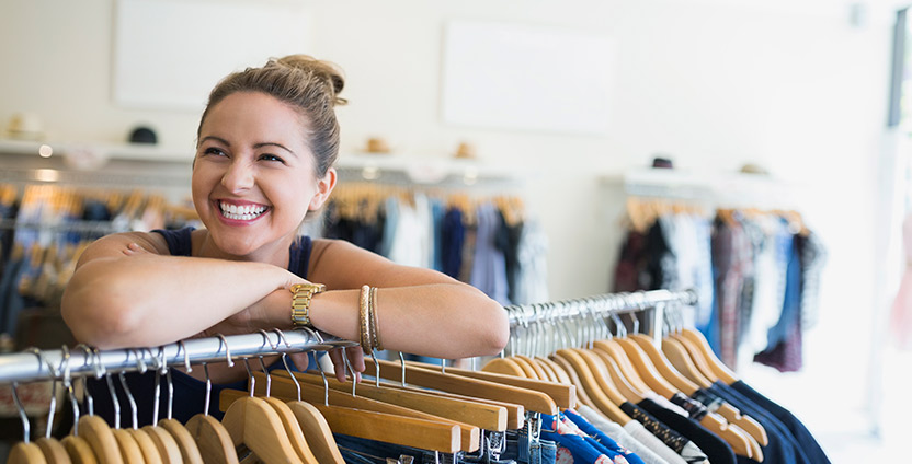 Woman leaning on clothes rack in shop