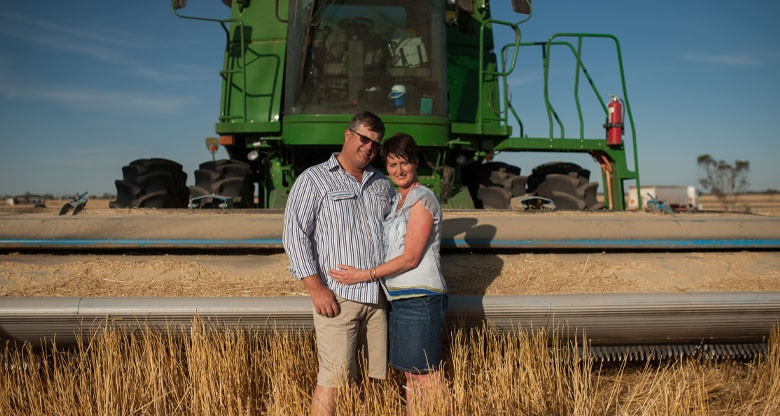 Mark and Merridee Schilling stand in front of farm machinery