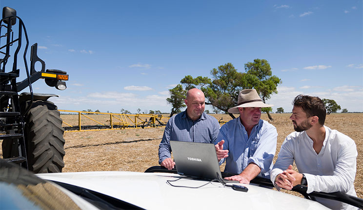 Three men working at a laptop on the hood of a car in a paddock