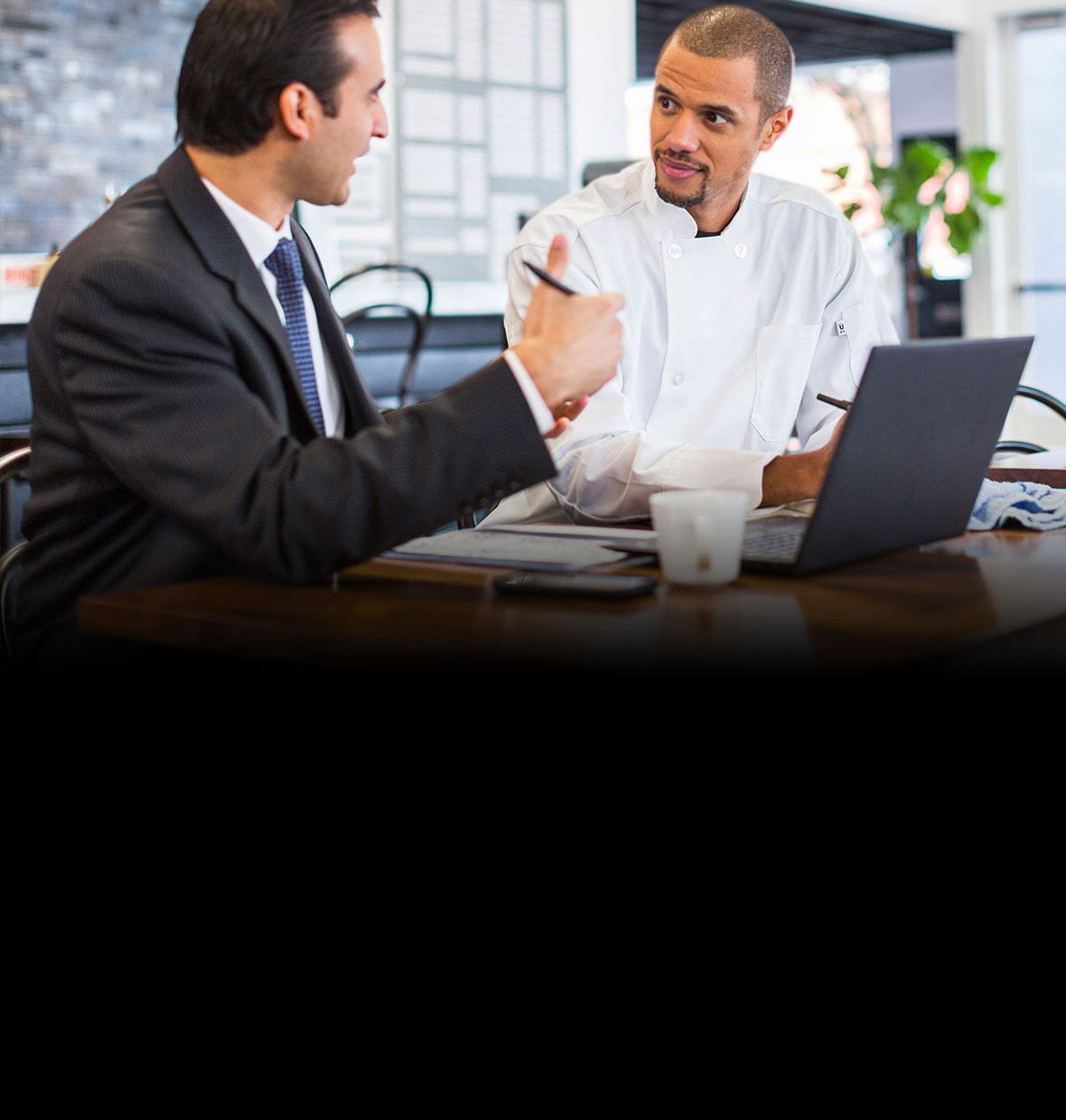 A business man and a chef sit discussing matters in front of a laptop in a restaurant.
