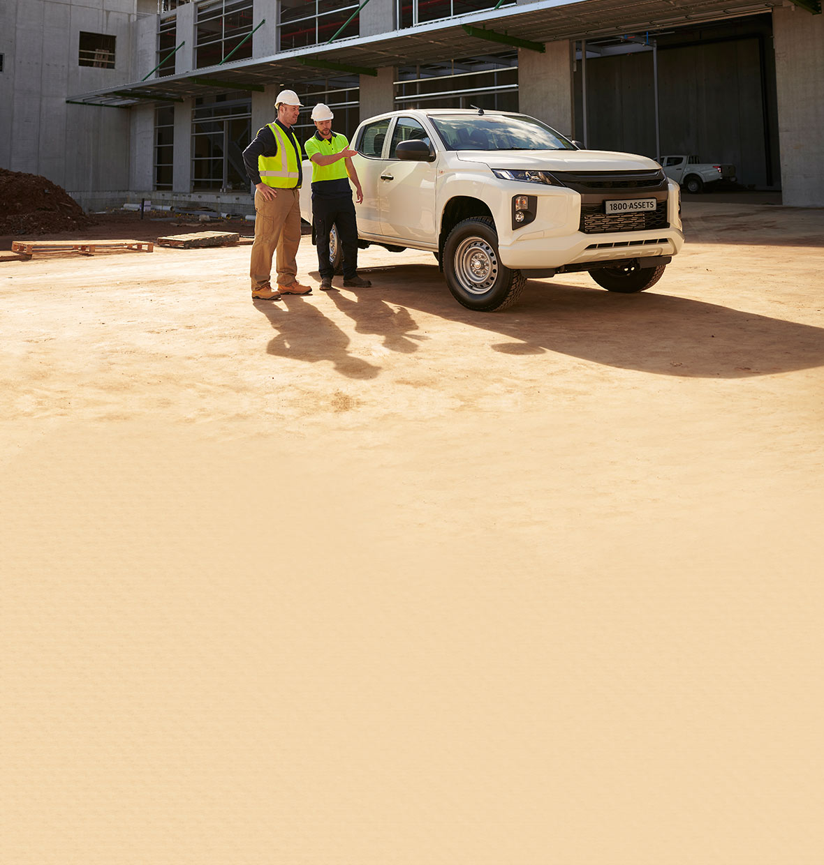 Two tradies stand triumphantly in front of a newly financed ute.
