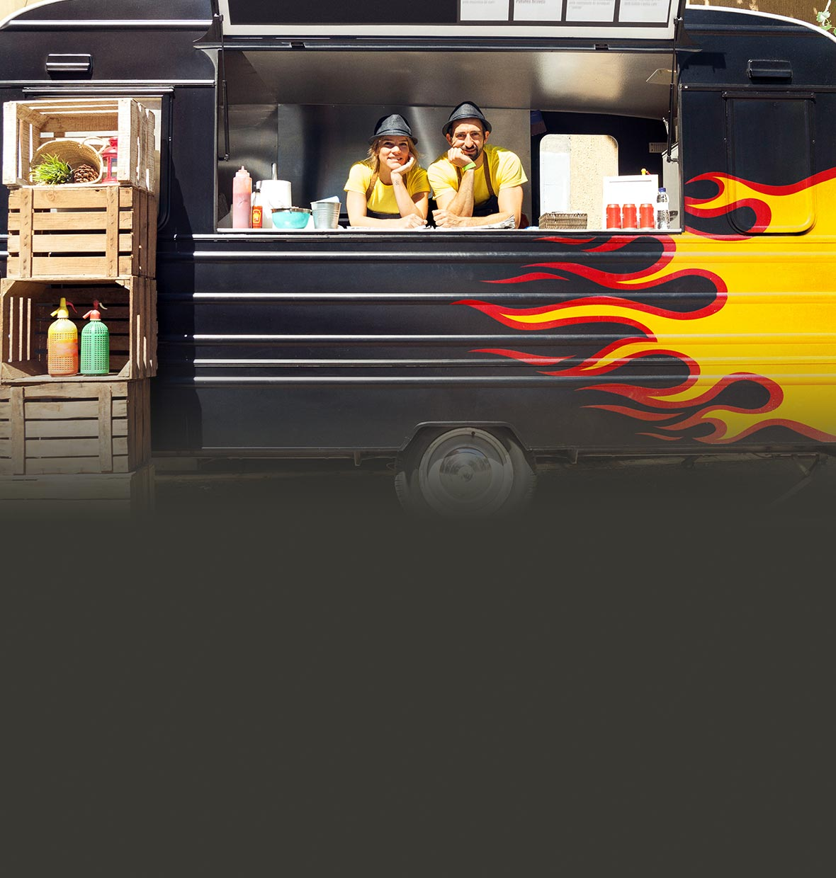 A couple working in a food truck with a flame painted on the side