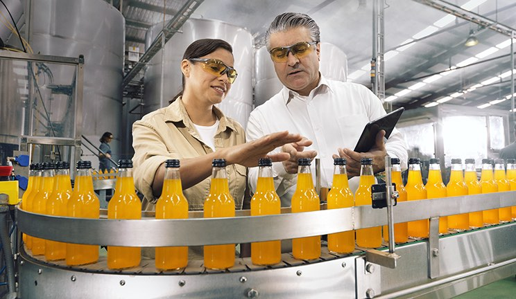 Man and woman standing next to a bottle production line