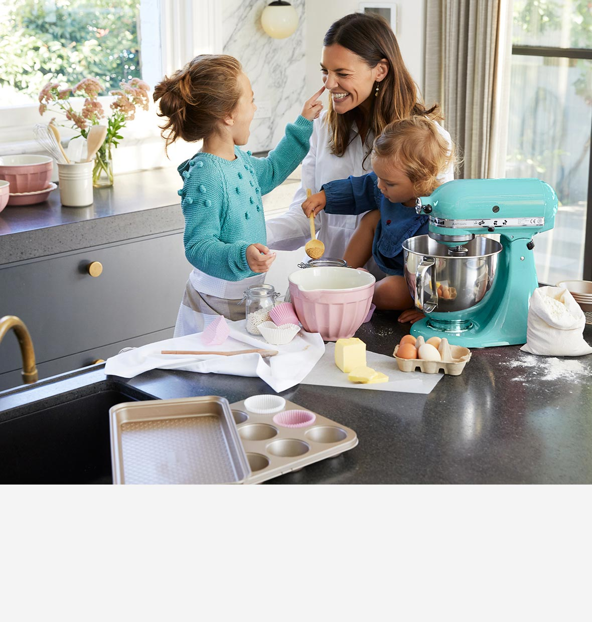 Mother in kitchen teaching her kids how to bake + Myer logo