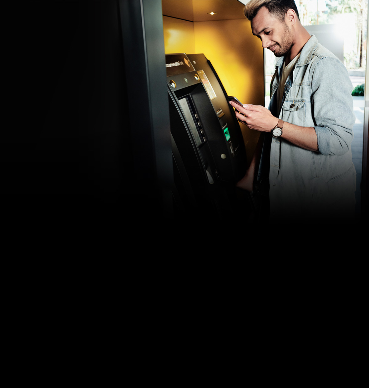 Image of person at a CommBank ATM, with mobile phone in hand