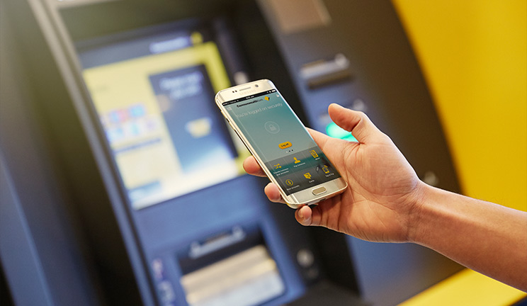 Mobile phone with CommBank app, near an ATM