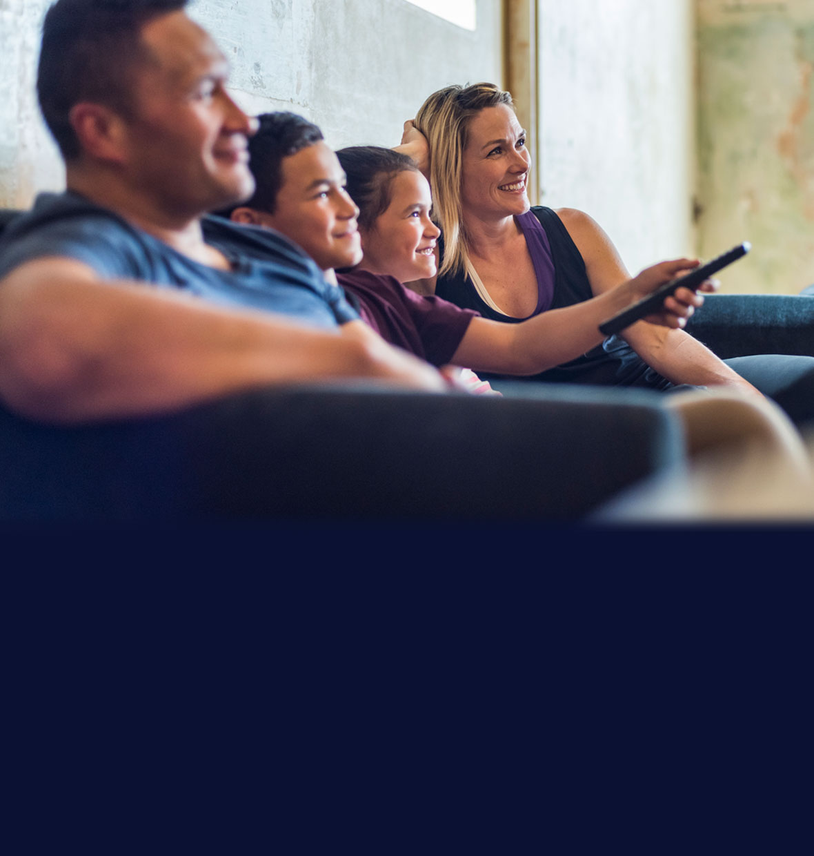 Family watching TV on couch