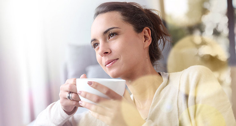 Thinking woman with cup of coffee