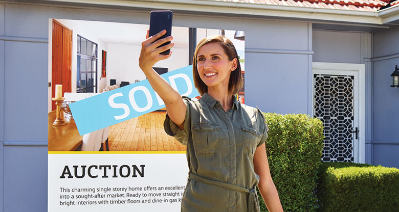 lady taking picture with sold sign