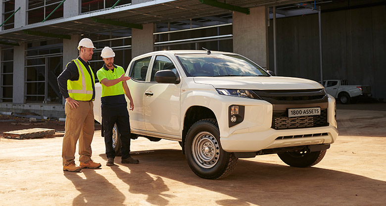 Two men in high vis standing in front of newly financed ute