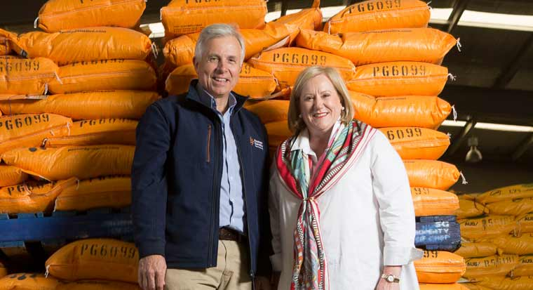 rob and ann damin standing in front of a pile of seed sacks