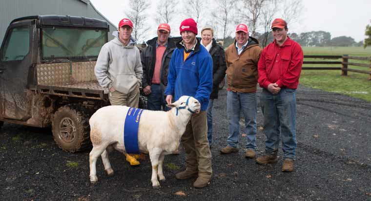 family of farmers standing with a prize winning sheep