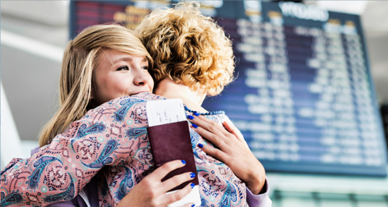 Mother and daughter hugging at the airport