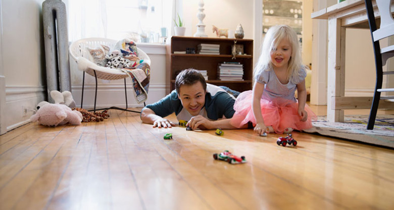 father and daughter playing with toy cars