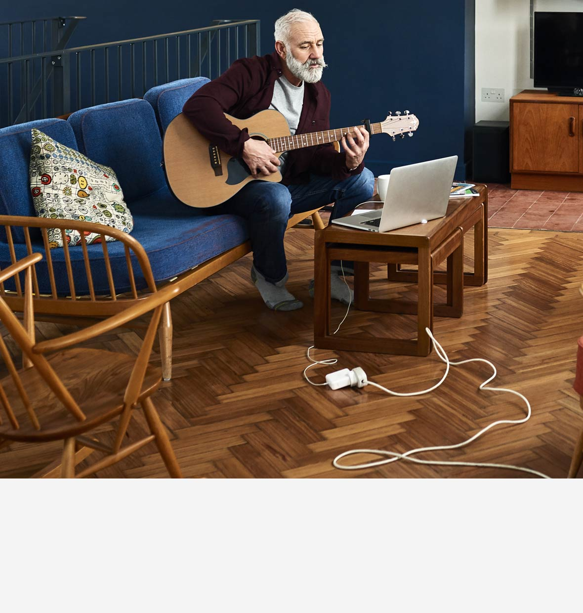 Man playing guitar in his lounge