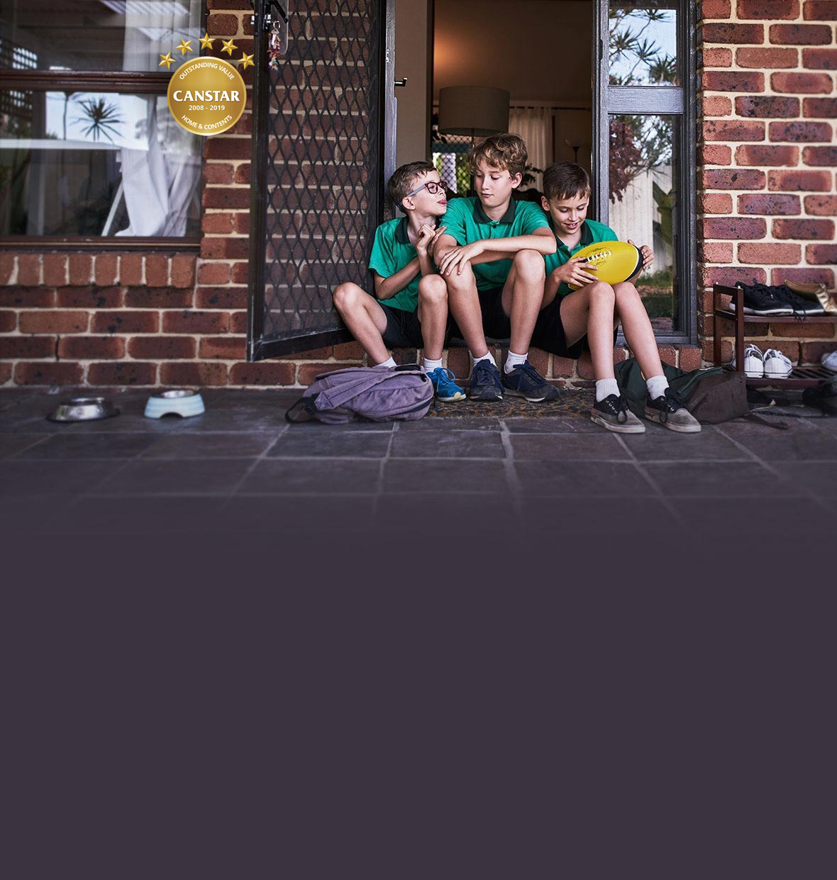 Three brothers sitting on the doorstep of their home after school