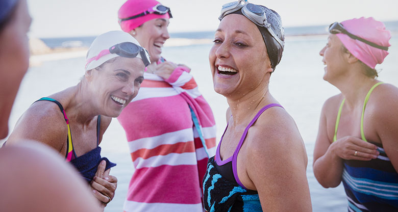 A group of women in swimming gear laughing on a beach