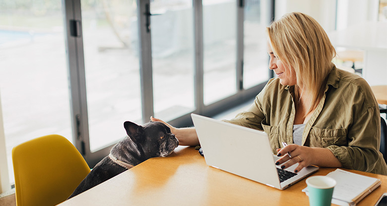 woman working from home with laptop and dog