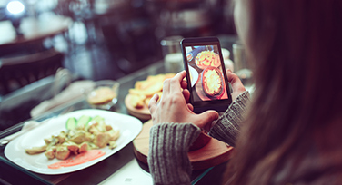 Girl taking photo of delicious food
