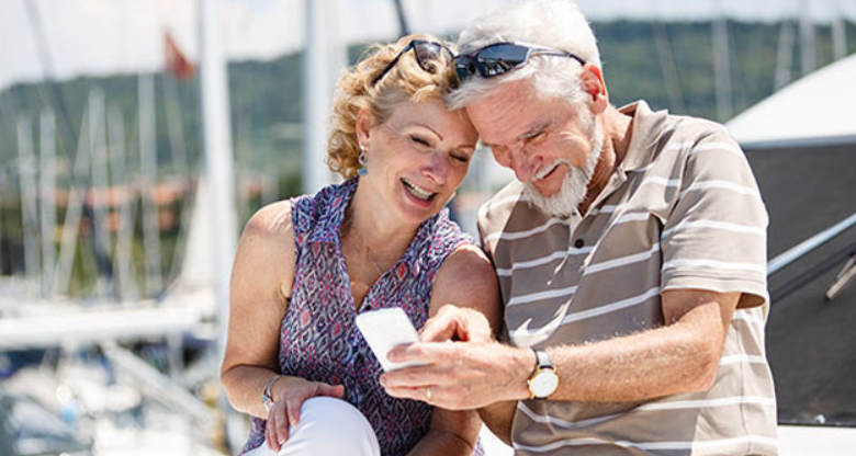 An senior couple looking at their phone on a marina