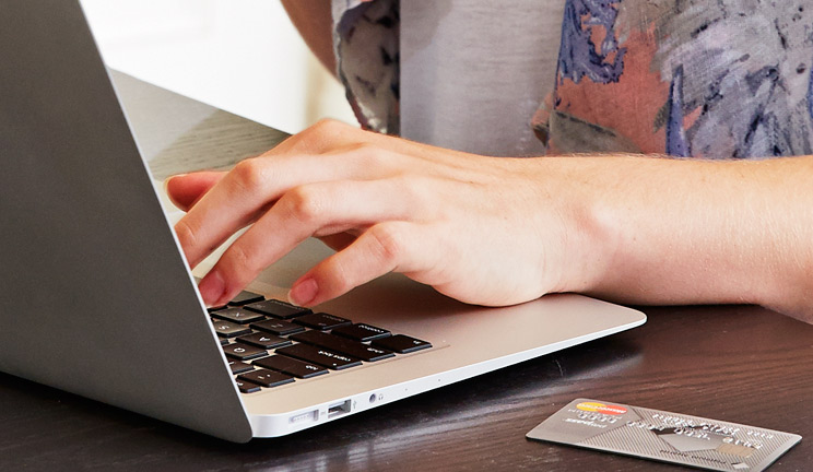 Photo of hands at laptop with a credit card