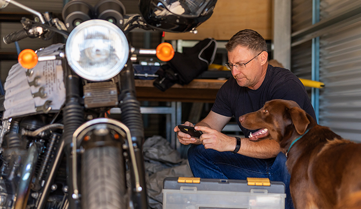 Man in his garage with a motorbike and dog