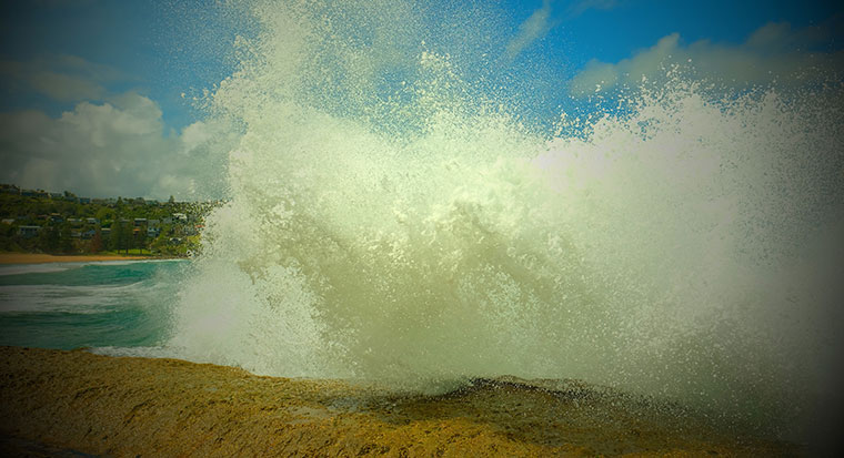 Wave smashing against rocks at the beach