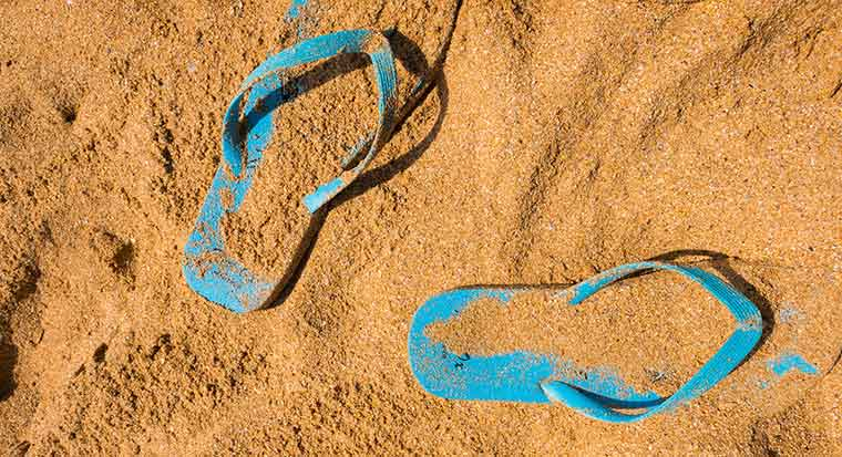 flip flop thongs in the sand on a beach