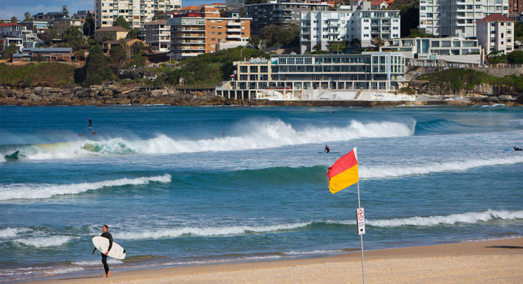 Surfer on Australian beach with Surf Life Saving red and yellow flag