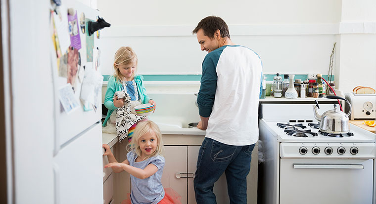 Father with young daughters in home kitchen