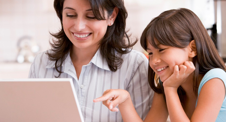 woman and female child look at laptop computer screen