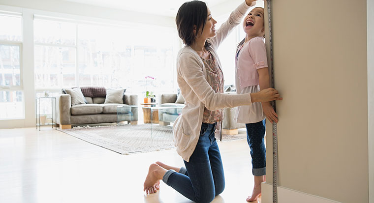 Mother measuring daughter's growth at home