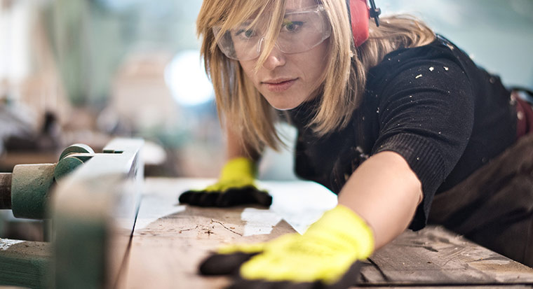 Woman wears safety goggles doing carpentry