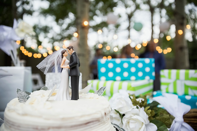 Close up shot of a wedding cake and bride and groom cake topper
