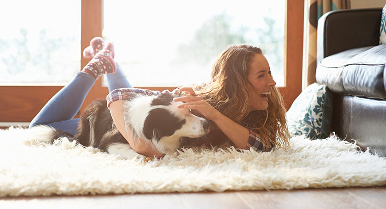 Woman on floor of home with dog