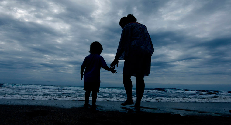 Parent and child hold hands playing at the beach