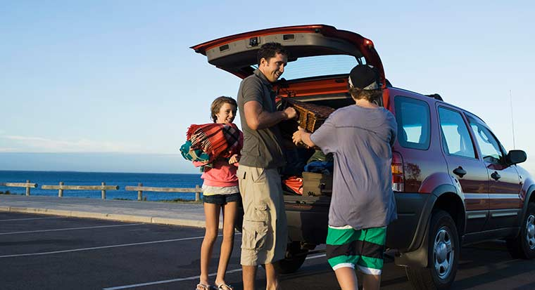Man and children unpack car at beach
