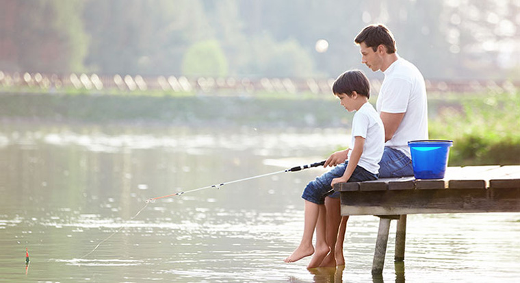Father fishing with son on lake