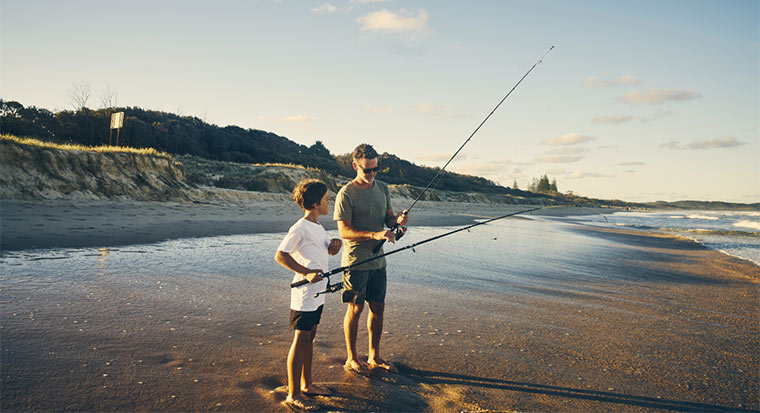 Father and son fishing on beach